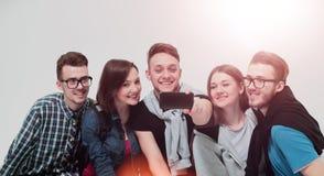 Il gruppo di giovani che si siedono sul banco, sorride ed invia una s Fotografia Stock