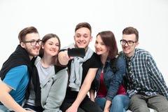 Il gruppo di giovani che si siedono sul banco, sorride ed invia una s Immagini Stock