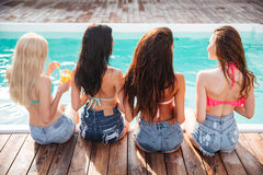 Il gruppo di giovani donne felici che bevono i cocktail si avvicina alla piscina Fotografia Stock