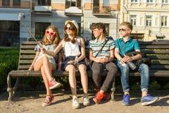 Il gruppo di gioventù sta divertendosi insieme all'aperto nel fondo urbano Vacanze estive, istruzione, concetto adolescente immagine stock libera da diritti