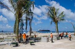 Il gruppo di lavoratori riunisce la sabbia sul cantiere facendo uso delle pale Immagine Stock
