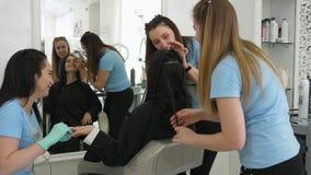 Il gruppo di lavoro del salone di bellezza fa l'acconciatura durante il manicure e compensa il cliente all'interno archivi video