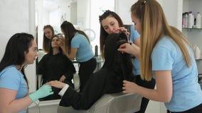 Il gruppo di lavoro dello studio di bellezza manicure durante trucco e le acconciature per il cliente allo studio