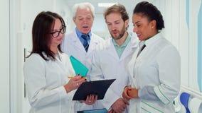 Il gruppo di medici esamina la lavagna per appunti immagine stock