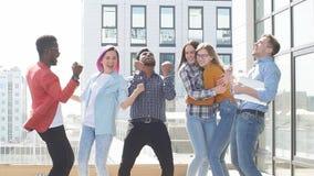 Il gruppo di multi giovani colleghi etnici celebra il successo sul terrazzo dell'ufficio moderno archivi video