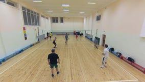 Il gruppo di pallavolo attivamente gioca nella palestra della scuola video d archivio