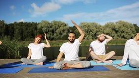 Il gruppo di persone che fanno l'yoga si esercita all'aperto video d archivio