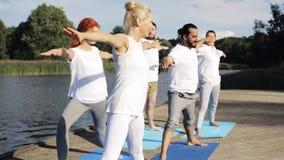 Il gruppo di persone che fanno l'yoga si esercita all'aperto stock footage