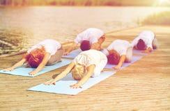 Il gruppo di persone che fanno l'yoga si esercita all'aperto Immagine Stock