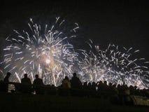 Il gruppo di persone che godono dei fuochi d'artificio bianchi spettacolari mostra in un carnevale o in una festa immagini stock