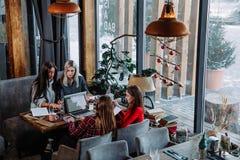 Il gruppo di persone che lavorano all'affare proietta al caffè, sedentesi alla tavola con i fogli di carta ed il computer portati Fotografia Stock