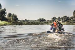 Il gruppo di persone che navigano sull'imbarcazione a motore dal fiume nel giorno di estate alla caccia si accampa durante la sta immagini stock