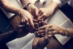 Il gruppo di persone che si tengono per mano che prega il culto crede immagine stock