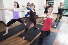 Il gruppo di persone con yoga facente stesa di armi durante l'yoga classifica Immagine Stock