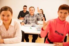 Il gruppo di persone dell'età differente che si siedono nell'aula ed assiste Immagini Stock