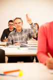 Il gruppo di persone dell'età differente che si siedono nell'aula ed assiste Fotografie Stock