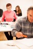 Il gruppo di persone dell'età differente che si siedono nell'aula ed assiste Fotografia Stock