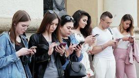 Il gruppo di persone facendo uso del telefono cellulare, pratica il surfing Internet, gioca il gioco ed utilizzare il app video d archivio