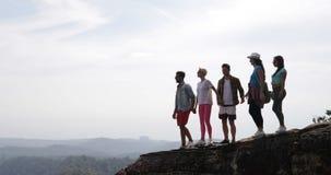 Il gruppo di persone le mani sollevate tenuta sulla cima della montagna gode degli uomini felici di libertà e dei turisti delle d video d archivio