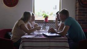 Il gruppo di persone si siede in ristorante e conversa archivi video