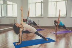Il gruppo di persone sta facendo l'yoga all'interno Fotografia Stock