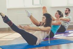 Il gruppo di persone sta facendo l'yoga all'interno Fotografie Stock
