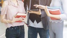 Il gruppo di persone tiene il libro e l'uso ed il tocco stazionari Immagini Stock