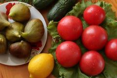 Il gruppo di pomodori con le gocce di acqua su una lattuga va Limone, cetrioli e fichi in un piatto della porcellana su una tavol Immagini Stock Libere da Diritti