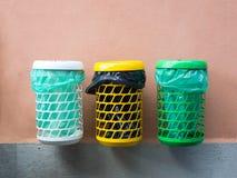 Il gruppo di pubblico variopinto ricicla i recipienti su una parete Fotografia Stock Libera da Diritti
