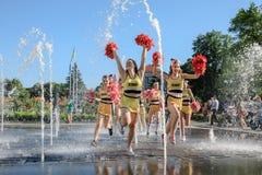Il gruppo di ragazze pon pon felici gode di di pareggiare tramite la fontana Fotografie Stock