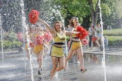 Il gruppo di ragazze pon pon felici gode di di pareggiare tramite la fontana Immagini Stock