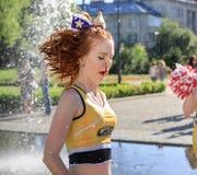 Il gruppo di ragazze pon pon felici gode di di pareggiare tramite la fontana Fotografia Stock Libera da Diritti
