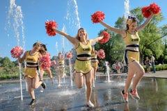Il gruppo di ragazze pon pon felici gode di di pareggiare tramite la fontana Fotografie Stock Libere da Diritti