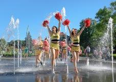 Il gruppo di ragazze pon pon felici gode di di pareggiare tramite la fontana Fotografia Stock