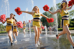 Il gruppo di ragazze pon pon felici gode di di pareggiare tramite la fontana Immagini Stock Libere da Diritti