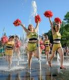 Il gruppo di ragazze pon pon felici gode di di pareggiare tramite la fontana Immagine Stock