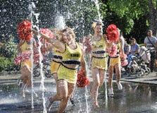 Il gruppo di ragazze pon pon felici gode di di pareggiare tramite la fontana Immagine Stock Libera da Diritti
