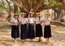 Il gruppo di ragazze tailandesi felici con la corona del fiore invita gli ospiti a visitare il paese fotografia stock