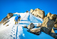 Il gruppo di scalatori raggiunge la cima del picco di montagna Scalata e Fotografie Stock Libere da Diritti