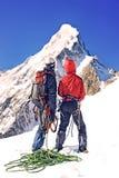 Il gruppo di scalatori raggiunge la cima del picco di montagna Scalata e Immagini Stock