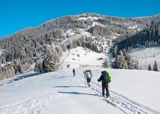 Il gruppo di sciatori aumenta in salita Immagine Stock