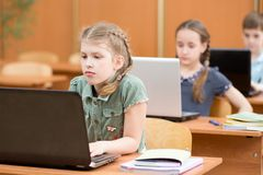 Il gruppo di scuola elementare scherza il lavoro insieme nella classe del computer immagine stock libera da diritti