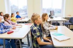 Il gruppo di scuola scherza con i taccuini in aula Fotografia Stock