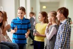 Il gruppo di scuola scherza con le latte di soda in corridoio Immagini Stock Libere da Diritti