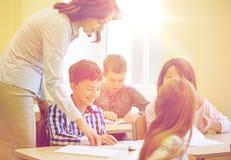 Il gruppo di scuola scherza la prova di scrittura in aula Immagini Stock