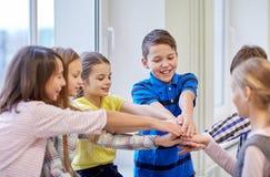 Il gruppo di scuola sorridente scherza mettere le mani sulla cima Immagini Stock Libere da Diritti