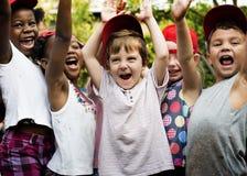 Il gruppo di sorridere di felicità sollevato mano degli amici della scuola dei bambini impara fotografia stock