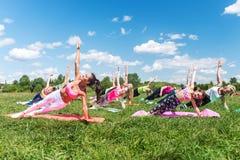 Il gruppo di sponda andante delle ragazze di misura si esercita in natura un giorno soleggiato Immagine Stock