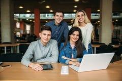 Il gruppo di studenti di college che studiano nella biblioteca di scuola, una ragazza e un ragazzo stanno utilizzando un computer Immagini Stock Libere da Diritti