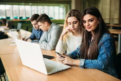 Il gruppo di studenti di college che studiano nella biblioteca di scuola, una ragazza e un ragazzo stanno utilizzando un computer Fotografia Stock